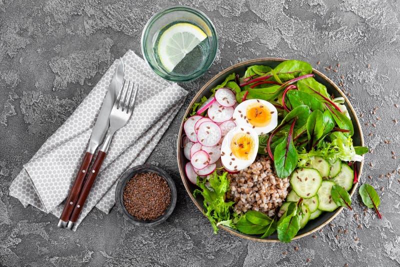 菩萨碗盘用荞麦粥,熟蛋,萝卜、黄瓜、莴苣和唐莴苣叶子新鲜蔬菜沙拉  健康 图库摄影