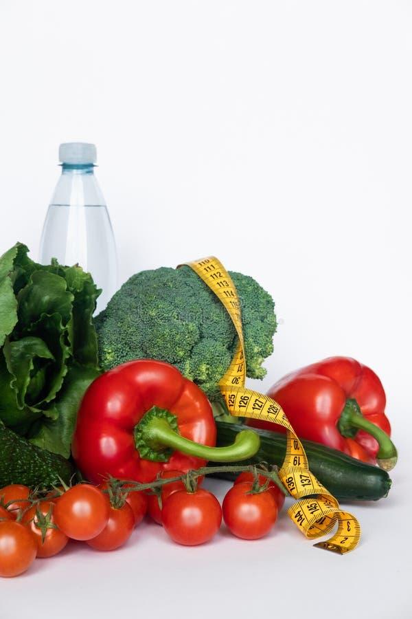 菜和水与磁带线在白色背景 健康概念的食物 复制空间 库存图片
