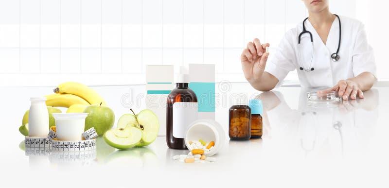 营养师医生在他的手显示药片在书桌办公室用苹果、果子、酸奶、磁带米和补充药物, 库存图片