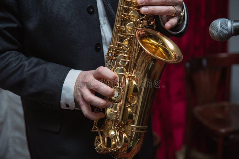 萨克管演奏员 弹萨克斯管的萨克斯管吹奏者手 女低音有爵士音乐仪器的萨克斯管演奏员 库存照片