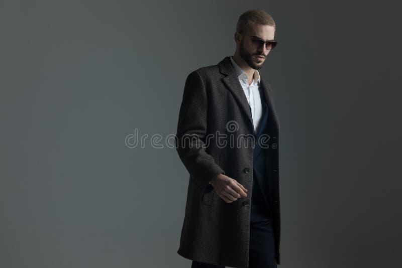 衣服的白肤金发的人与太阳镜和longcoat走 库存图片