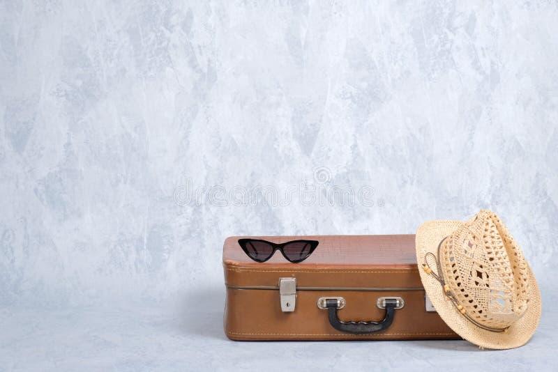 行家女性旅行家时髦的古板的辅助部件:葡萄酒太阳镜,草帽,在灰色背景的皮革手提箱 免版税库存照片
