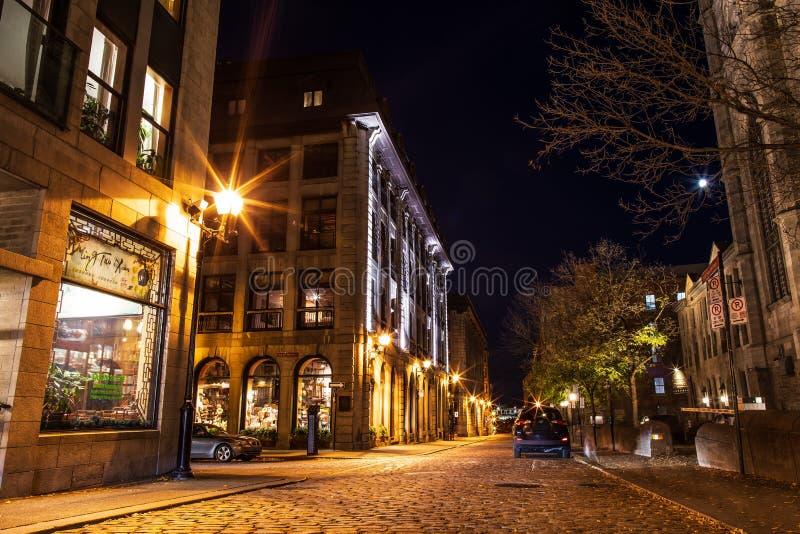 街道和历史大厦在旧港口古迹从蒙特利尔,夜视图的 蒙特利尔老都市建筑学  库存照片