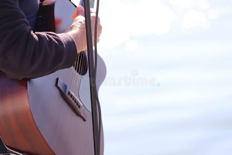 街道音乐家 音乐家的手的片段在一把吉他的以蓝色海为背景在一好日子 库存照片