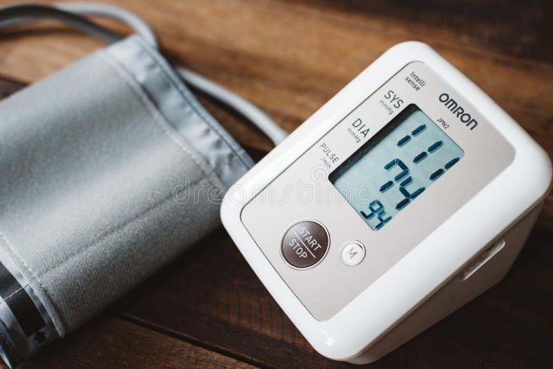 血压计或电子血压从品牌欧姆龙在木 免版税库存照片