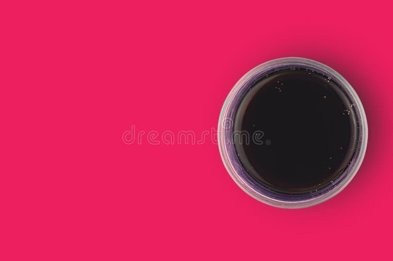 被供气的可乐黑色一块充分的玻璃与泡影的在烹调的红色桌上 复制您的文本的空间 顶视图 库存照片