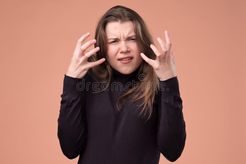 被激怒的女孩有效地使面孔表示,姿态生气 免版税图库摄影