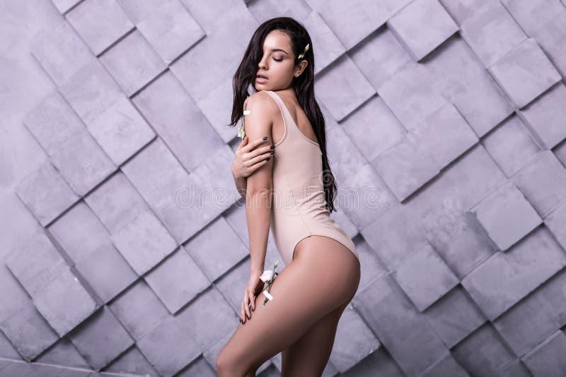 被拍摄在紫罗兰色背景的年轻吸引的时装模特儿 免版税库存照片