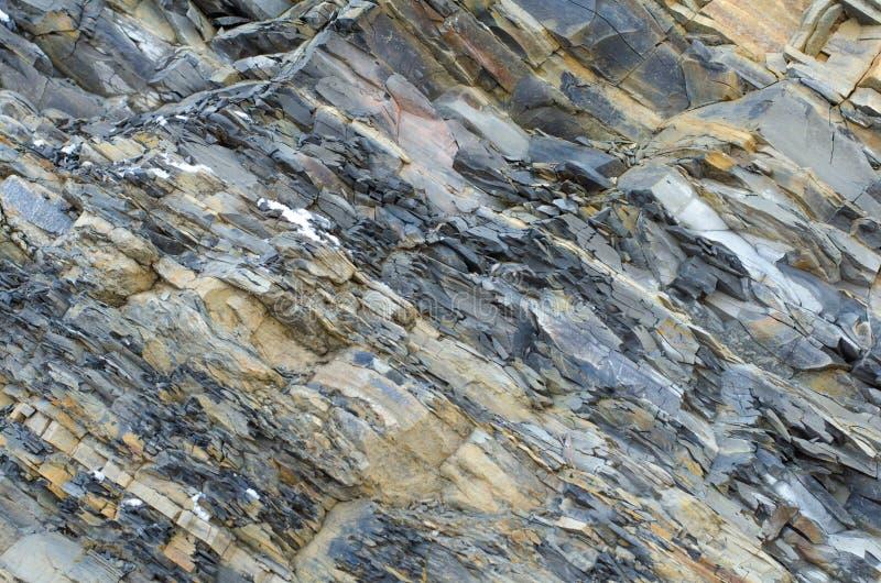 被碾压的石头 灰色黄色板岩特写镜头背景 免版税库存图片
