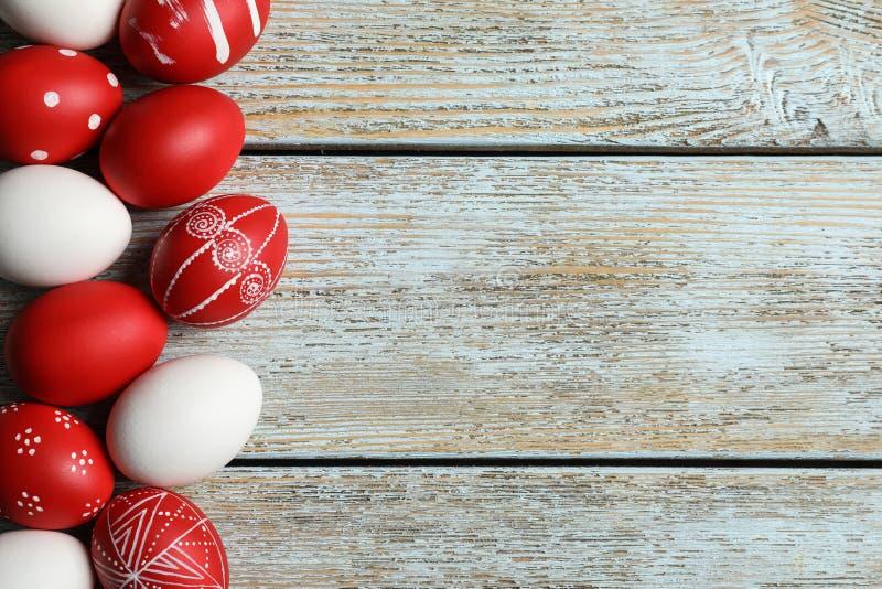 被绘的红色复活节彩蛋的平的被放置的构成在木桌上的 免版税库存图片