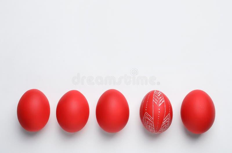 被绘的红色复活节彩蛋的构成在白色,顶视图的 免版税库存照片