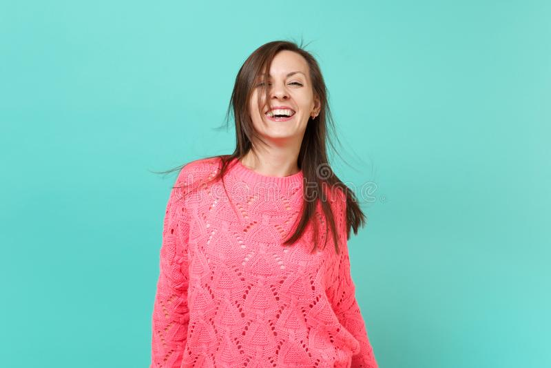 被编织的桃红色毛线衣的快乐的美丽的年轻女人有在蓝色绿松石墙壁背景隔绝的振翼的头发的 图库摄影