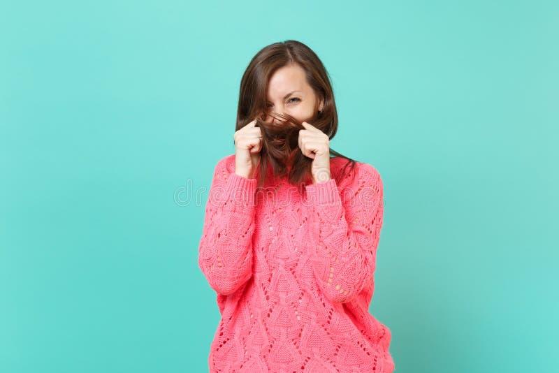 被编织的桃红色毛线衣覆盖物面孔的快乐的逗人喜爱的年轻女人与在蓝色绿松石墙壁背景隔绝的她的头发 免版税库存图片