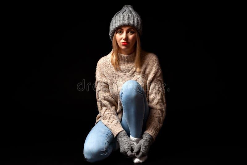 被编织的手套和帽子的在灰色,蓝色牛仔裤年轻美丽的白肤金发的女孩,米黄毛线衣坐与盘的腿的地板和 图库摄影