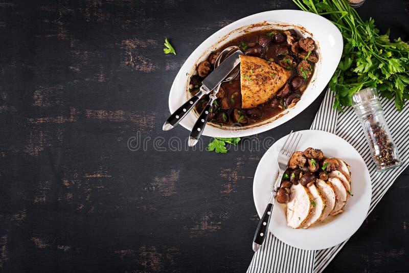 被烘烤的鸡胸脯用在芳香抚人的调味汁的蘑菇在桌上 免版税库存图片
