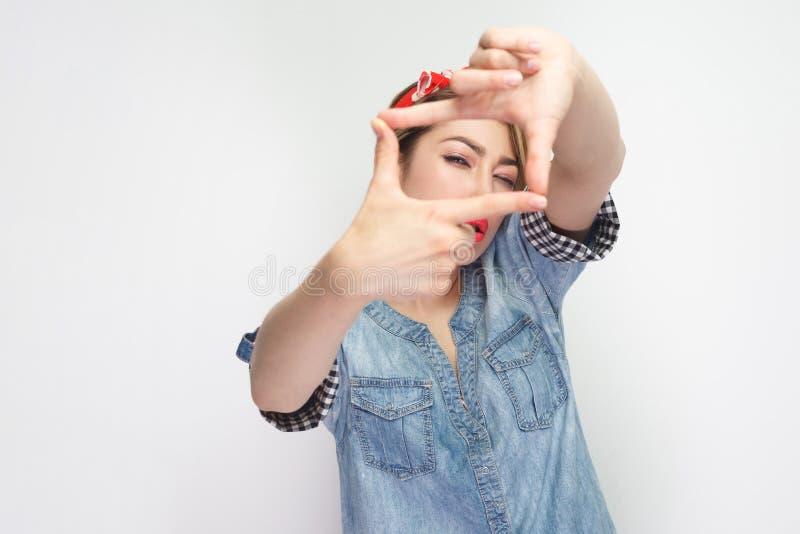 被聚焦的美丽的年轻女人画象偶然蓝色牛仔布衬衣的有与庄稼构成姿态的红色头饰带身分的和 免版税图库摄影