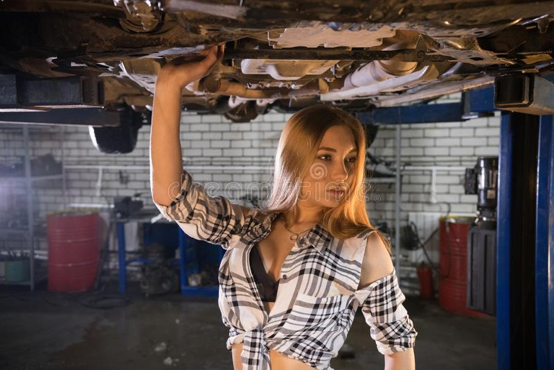 被解扣的镶边衬衣身分的年轻性感的技工妇女在汽车下在汽车修理服务中 免版税库存图片