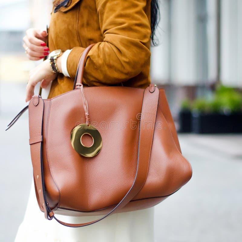 袋子特写镜头在女性手上 时髦的现代和女性图象,样式 一件夹克的女孩有一个皮革棕色袋子的 免版税图库摄影