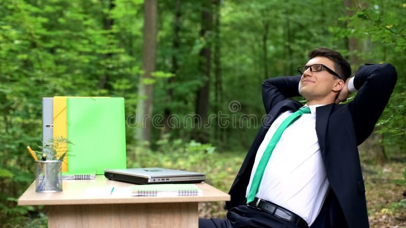 西装完成的工作的愉快的人和放松在绿色美丽的森林里 免版税库存照片