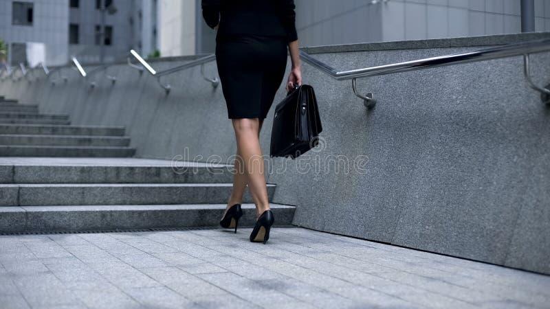 西装的走可爱的妇女在楼上,成功的事业的概念 免版税库存照片