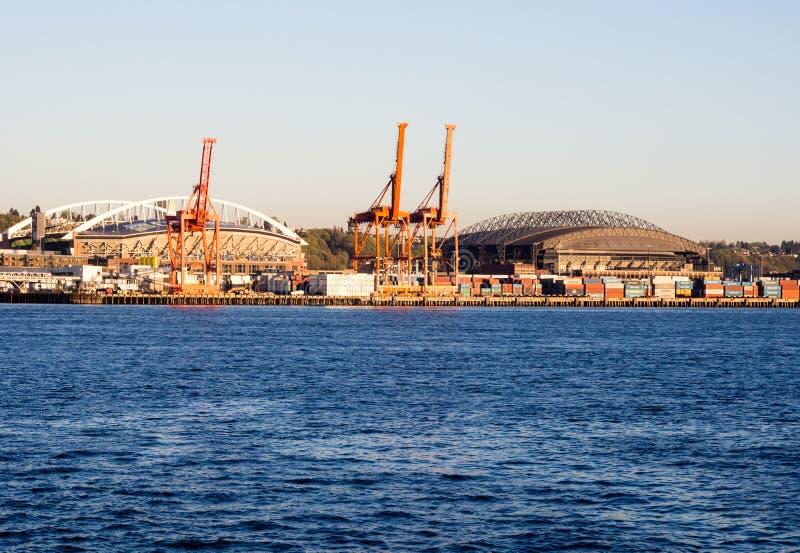 西雅图港日落的与货物起重机和CenturyLink领域 免版税图库摄影