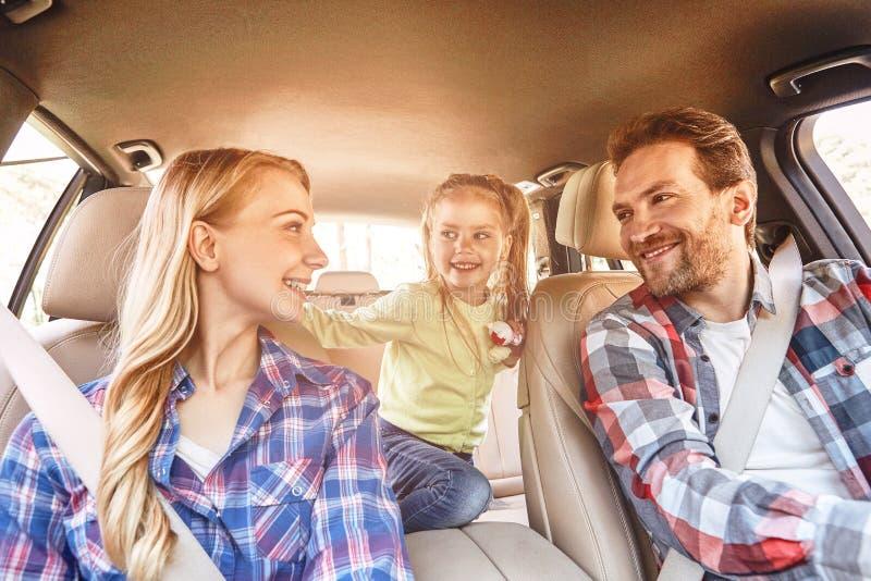 要移动是居住 坐在汽车和驾驶的微笑的家庭 家庭旅行 免版税库存照片