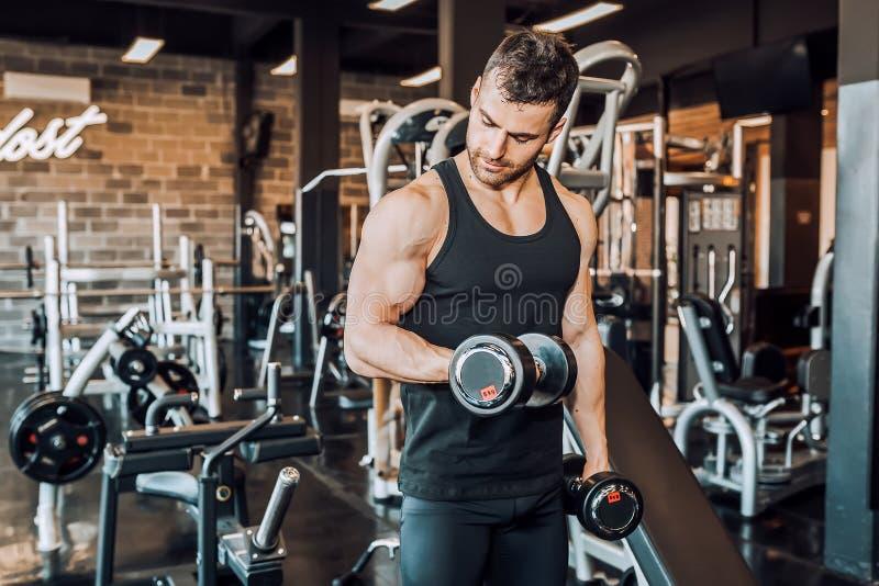 解决与在健身房的哑铃的坚定的肌肉人 免版税库存图片