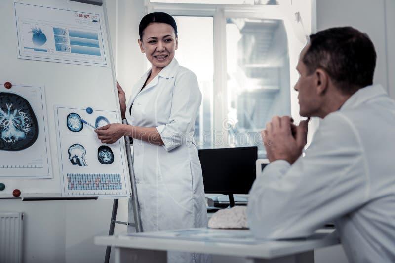 解释在脑子的科学家过程对她的同事 库存照片