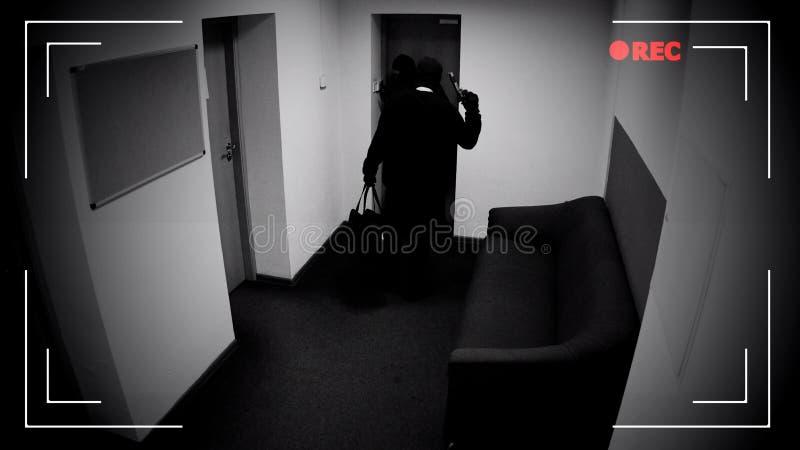 解除防盗报警器系统武装的两个危险被掩没的人,刹车入银行地下室 免版税库存图片