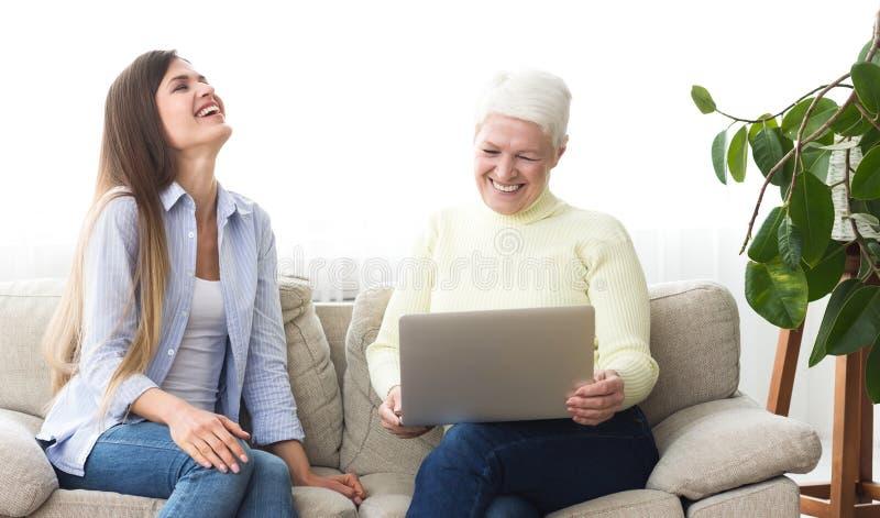 观看在膝上型计算机的母亲和女儿滑稽的录影 库存图片