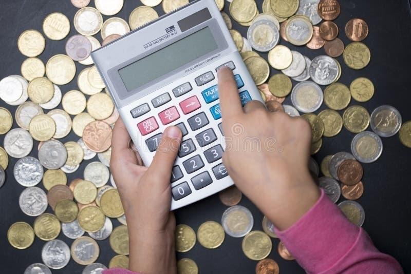 计数与计算器的在黑暗的背景的小女孩金钱和硬币 免版税库存照片