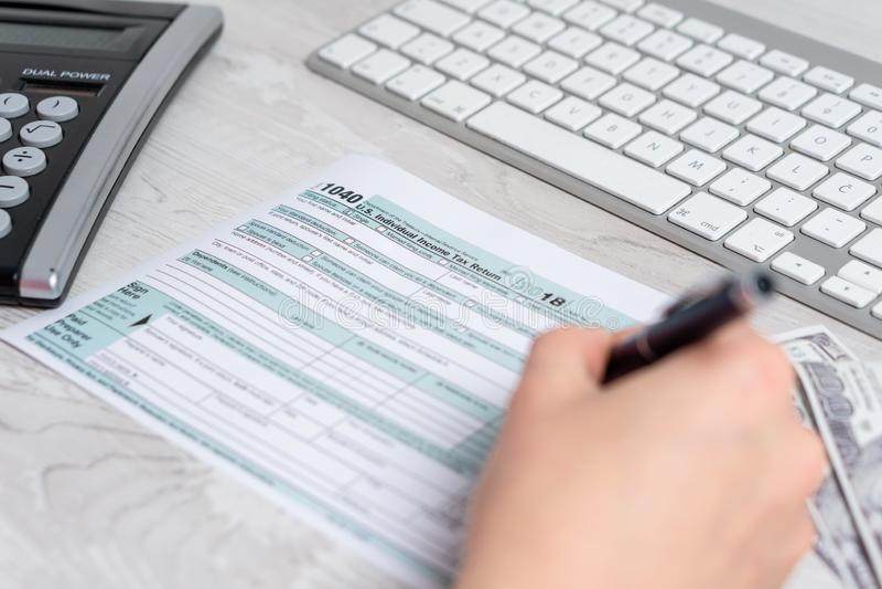 计算和填装美国报税表的手照片在键盘旁边、美金和报税表1040 4月15日 图库摄影