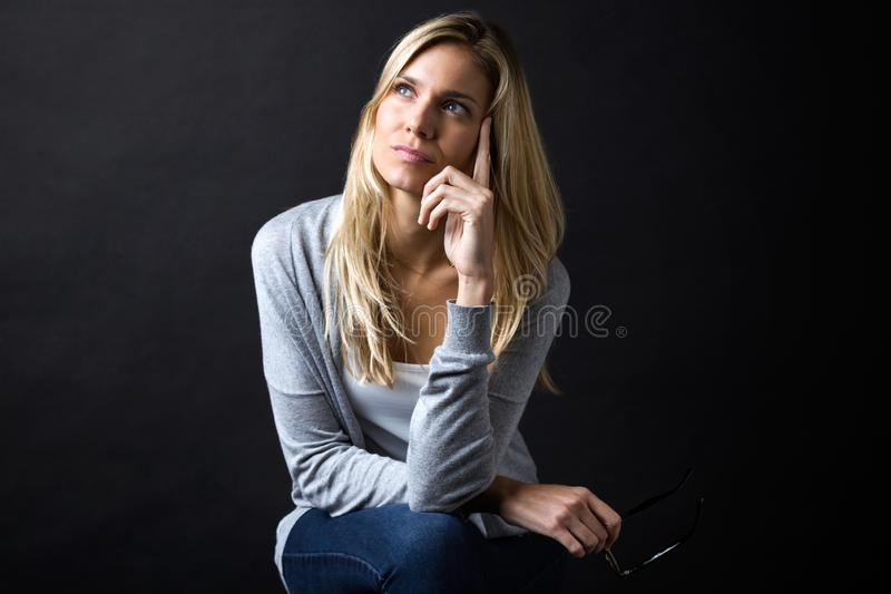 认为在她的忧虑的美丽的年轻女人,当拿着镜片被隔绝在黑色时 图库摄影