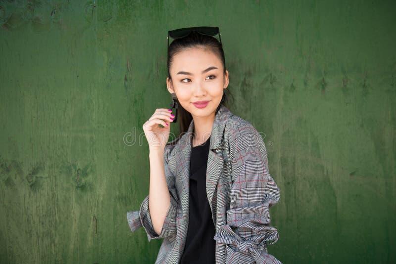 认为和微笑在绿色墙壁附近的逗人喜爱的退出的亚裔女孩看对边 免版税库存照片
