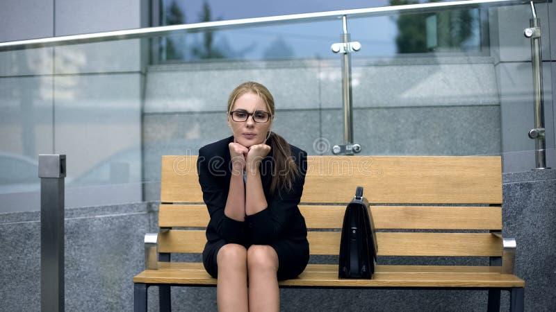 让烦恼的孤独的女商人坐长凳,担心从工作的解雇 免版税库存照片