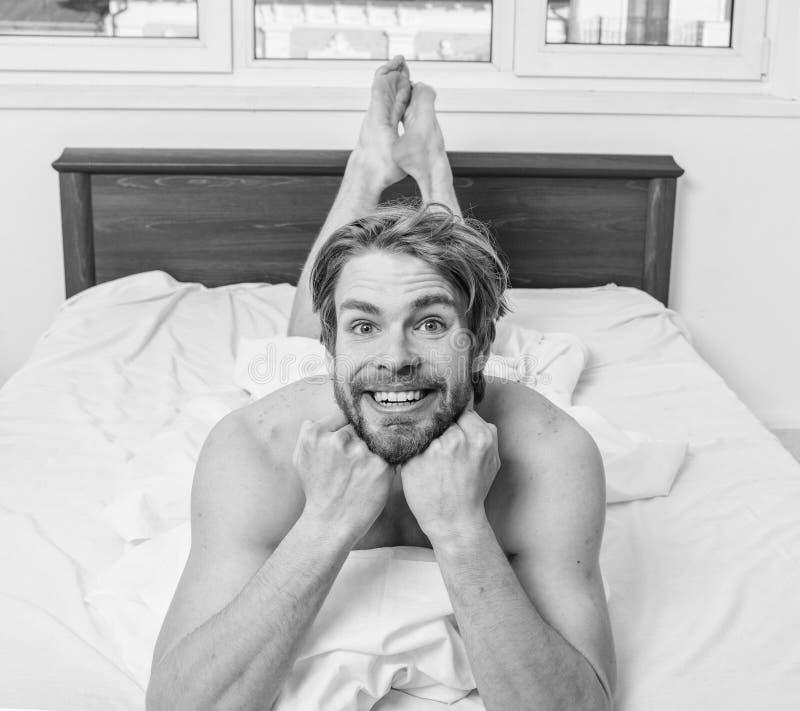 让舒适您的身体的感受 供以人员不剃须的英俊的愉快的微笑的躯干松弛床 白色人强壮男子的位置 免版税库存照片