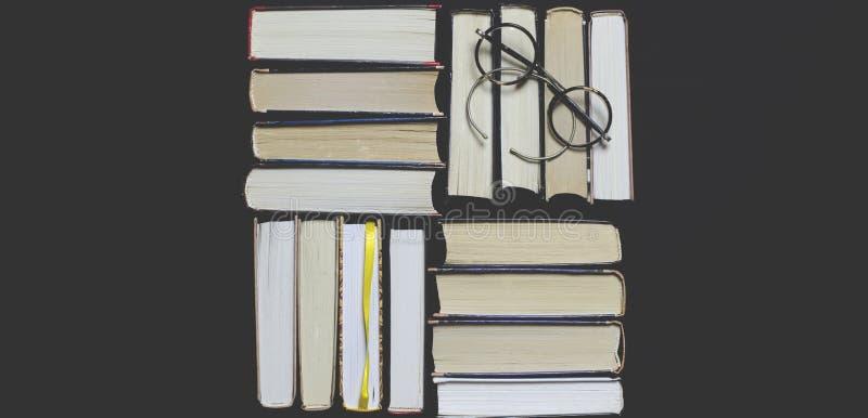 许多多彩多姿的厚实的开放在黑暗的背景书摊 在书是老圆的玻璃和一个开放笔记本有a的 免版税库存图片