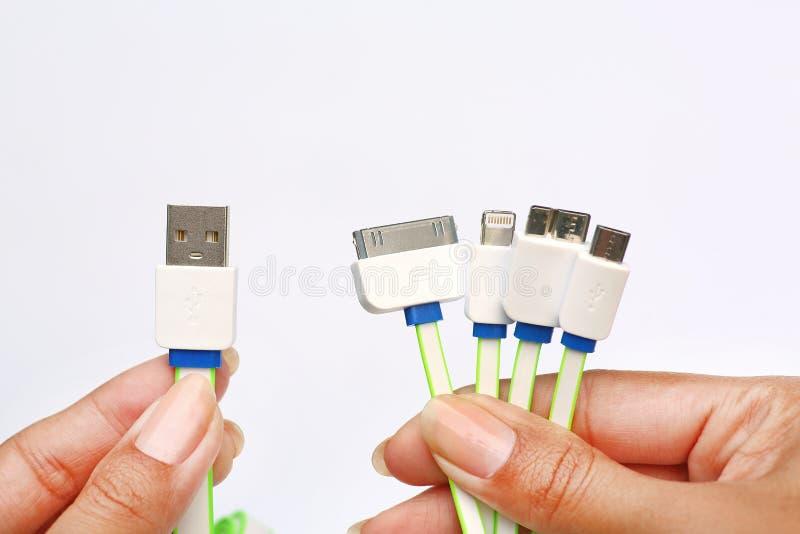 许多的手拿着在1个USB充电器的类型适配器在白色背景 普遍充电器 库存图片