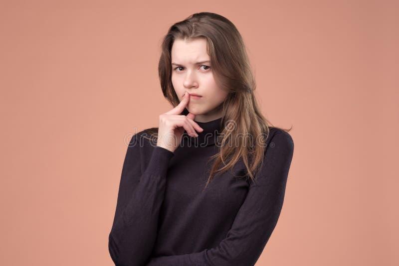设法想法的年轻女人做出一个正确的决定 免版税图库摄影