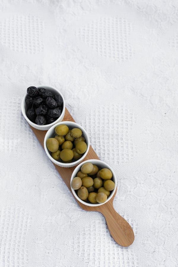 设置三个白色碗用在木盘子的橄榄在白色毯子 库存照片