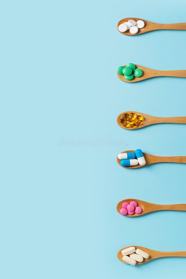 设置五颜六色的药片和片剂在匙子在蓝色背景 免版税库存照片