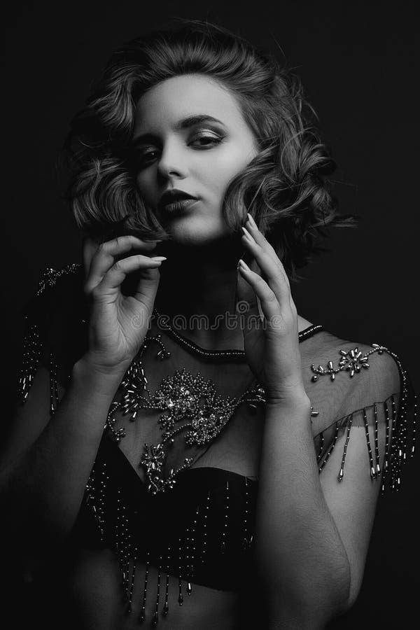 诱人的深色的模型画象与摆在与对比光的卷发和美好的构成的 黑白定调子 免版税库存图片