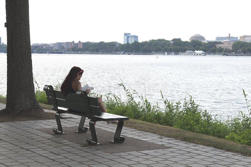 读一本书的女孩在公园在长凳在查理斯河附近在波士顿,马萨诸塞 免版税库存照片