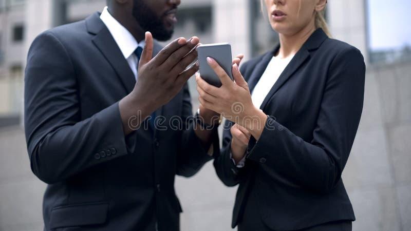 读从智能手机的办公室工作者前新闻,谈论业务会议 免版税库存照片