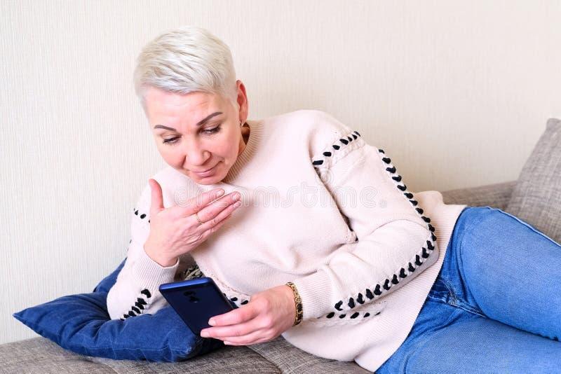 读在智能手机的女孩SMS 快乐的惊奇的情感 妇女的短的理发 时兴的时髦的外形与 库存图片