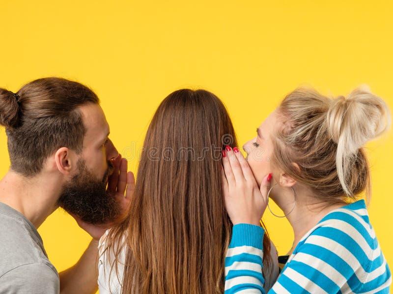 说服人妇女耳语女孩耳朵 免版税库存图片