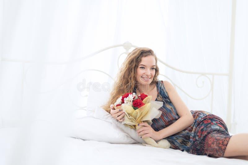 说谎在与花花束的床上的少妇 免版税库存图片