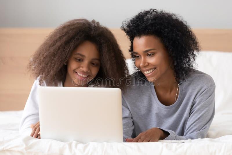 说谎在与青少年的女儿浏览互联网的床上的非洲母亲 免版税库存图片