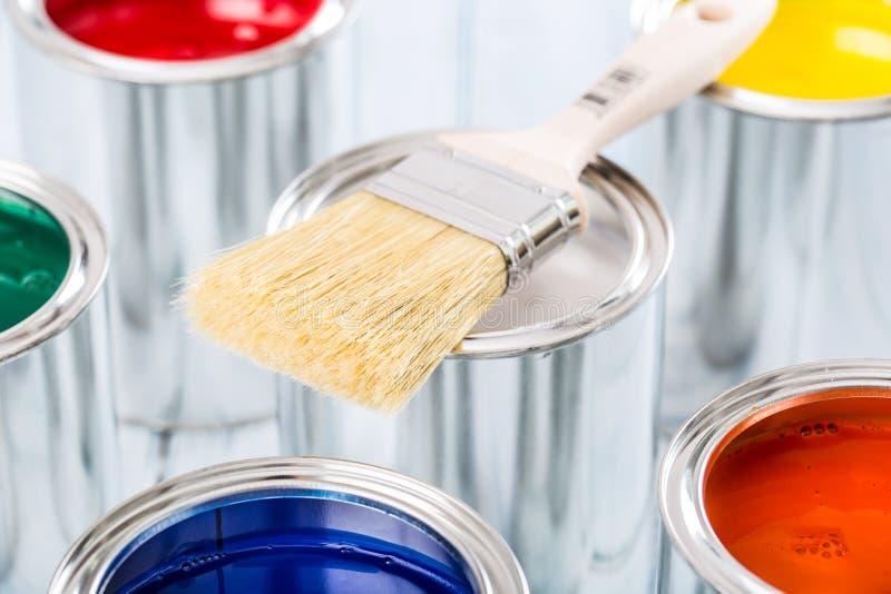 说谎在多彩多姿的油漆罐头的特写镜头刷子 库存照片