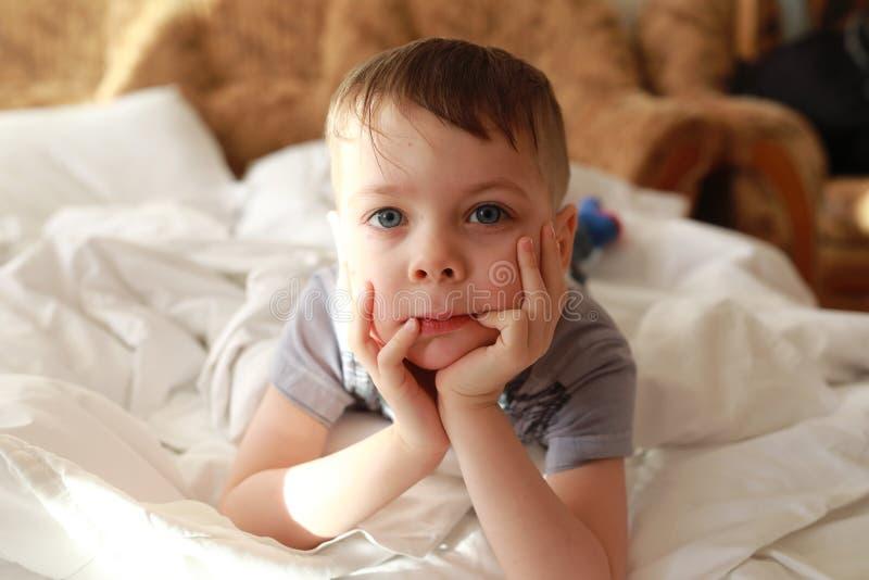 说谎在床上的男孩 免版税库存照片